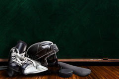 Ice Hockey Equipment and Chalk Board Copy Space. Ice hockey equipment consisting of skates, helmet, stick and puck with background chalk board copy space Royalty Free Stock Photos