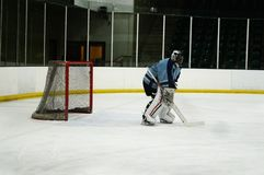 Ice Hockey Goaltender. A side view of just the goalie during a hockey practice stock photo
