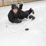 Ice hockey player. Ice hockey player boy in uniform sliding on ice holding stick out towards puck royalty free stock photography