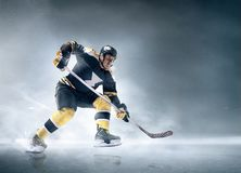 Ice hockey player in action. Decisive throw of the puck and goal. Ice hockey player in action on ice. Male professional athlete swinging his stick before a Stock Photo