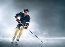 Ice hockey player in action. Decisive throw of the puck and goal. Ice hockey player in action on ice. Male professional athlete swinging his stick before a Stock Image