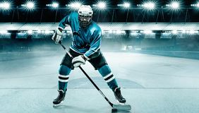 Ice Hockey player athlete in the helmet and gloves on stadium with stick. Action shot. Sport concept. Hockey player in the mask on stadium royalty free stock photos