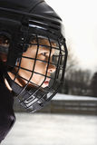 Ice hockey player boy. Ice hockey player boy in uniform and cage helmet concentrating royalty free stock photography