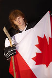 Ice hockey player with canadian flag. Ice hockey player holding canadian flag over black Royalty Free Stock Photo