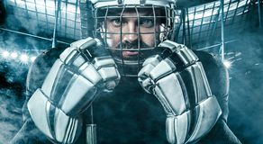 Ice Hockey player in the helmet and gloves on stadium with stick. Hockey player in the mask on stadium royalty free stock photography