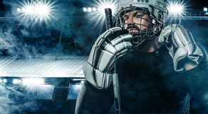 Ice Hockey player in the helmet and gloves on stadium with stick. Hockey player in the mask on stadium stock images