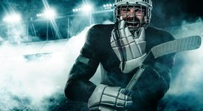 Ice Hockey player in the helmet and gloves on stadium with stick. Hockey player in the mask on stadium stock photo