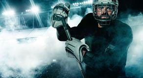 Ice Hockey player in the helmet and gloves on stadium with stick. Hockey player in the mask on stadium stock image