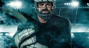 Ice Hockey player in the helmet and gloves on stadium with stick. Hockey player in the mask on stadium royalty free stock photo