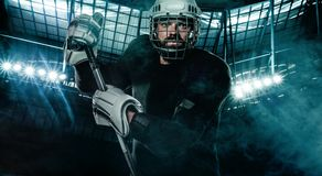 Ice Hockey player in the helmet and gloves on stadium with stick. Hockey player in the mask on stadium royalty free stock image