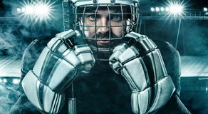 Ice Hockey player in the mask and gloves on stadium with stick. Hockey goalie in the mask royalty free stock photo