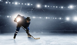 Ice hockey player at rink. Hockey player in lights at ice rink stock photos
