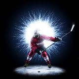 Ice Hockey player is skating on a abstract background. With intensional light Stock Photos