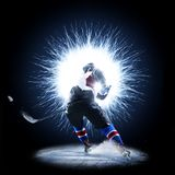 Ice Hockey player is skating on a abstract background. With intensional light Royalty Free Stock Image