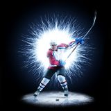 Ice Hockey player is skating on a abstract background. With intensional light Royalty Free Stock Images