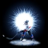 Ice Hockey player is skating on a abstract background. With intensional light Stock Photo