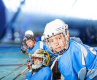 Ice hockey player with teammates during the match. Close-up portrait of happy boy in hockey uniform during the math on ice rink stock photo