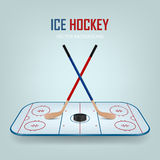Ice hockey puck and crossed sticks on field. Stock Image