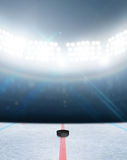 Ice Hockey Rink Stadium. A generic ice hockey ice rink stadium with a frozen surface and a hockey puck under illuminated floodlights Royalty Free Stock Images