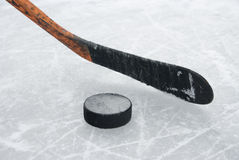Ice hockey stick and puck on ice. The orange ice hockey stick and puck on ice Stock Image