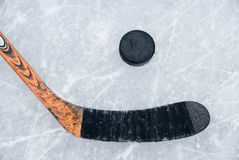 Ice hockey stick and puck on ice. The orange ice hockey stick and puck on ice Stock Photography