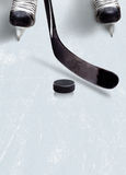 Ice hockey stick and puck on ice with copy space. Stock Photography