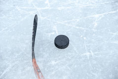 Ice hockey stick and puck. An orange ice hockey stick and a puck on ice Royalty Free Stock Image