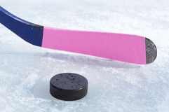 Ice hockey stick and puck. Ice hockey stick with pink tape and puck Royalty Free Stock Image