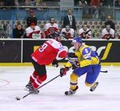 Ice Hockey 2017 World Championship Div 1 in Kyiv, Ukraine. KYIV, UKRAINE - APRIL 25, 2017: Martin SCHUMNIG of Austria L fights for a puck with Vitali LYALKA of Stock Photos