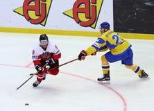 Ice Hockey 2017 World Championship Div 1 in Kyiv, Ukraine. KYIV, UKRAINE - APRIL 25, 2017: Martin ULMER of Austria L fights for a puck with Yuri PETRANGOVSKY of Stock Image