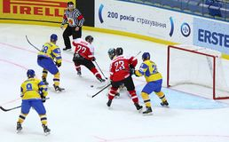 Ice Hockey 2017 World Championship Div 1 in Kyiv, Ukraine. KYIV, UKRAINE - APRIL 25, 2017: Ukrainian ice-hockey players Yellow jersey fight for a puck with Royalty Free Stock Photos