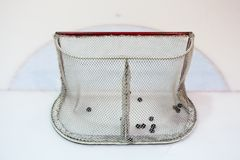 Ice hokey net filled with pucks. Seen from behind stock photos