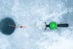 Ice-hole and rod for winter fishing. Royalty Free Stock Photos