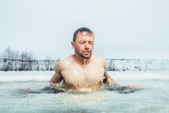 Ice hole swimming. Young man swimming in the winter lake in the ice hole stock image