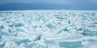 Ice hummocks on the northern shore of Olkhon Island on Lake Baikal. Transparent blocks of crystal clear ice crawl ashore. Royalty Free Stock Photo