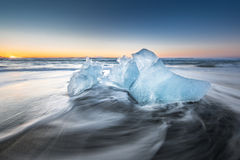 Ice on ice beach with water wave in Jokulsarlon, Iceland. Royalty Free Stock Images
