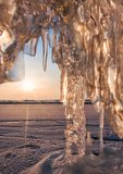 Ice with icicle, sky, sun and snow background Stock Photography