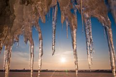 Ice with icicle, sky, sun and snow background Royalty Free Stock Photo