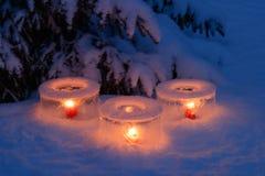 Ice lanterns. Candles burning inside ice lanterns under a garden spruce stock photo