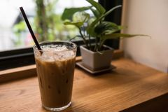 Ice Latte coffee near window. Ice Latte coffee and decorated plant on wooden table near window. Drink on cafe with copy space for text Stock Image