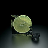Ice lemon. Melted ice cube with piece of lemon royalty free stock photos