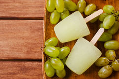 Ice lolly of green grapes. On a wooden background. Selective focus Royalty Free Stock Photography