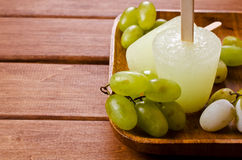 Ice lolly of green grapes. On a wooden background. Selective focus Stock Photos