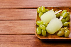 Ice lolly of green grapes. On a wooden background. Selective focus Stock Image