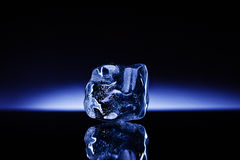 Ice magnitude!. A shapeless piece of ice on reflective surface against the deep blue glowing background Stock Photos