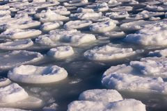 The ice melts, spring. Along the sea shore round ice floes, in the distance blue water. The beginning of spring, March, warming. Ice drift, sludge, snow melt Stock Photo
