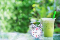 Ice milk green tea. And alarm clock with green blur background Stock Photos
