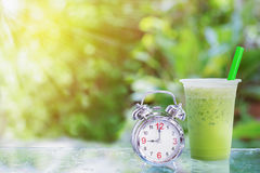 Ice milk green tea. And alarm clock with green blur background Stock Images