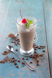 Ice Mocha / Chocolate Coffee drinks with whipped cream. Red cherry and mint on top, on rustic blue background Royalty Free Stock Image