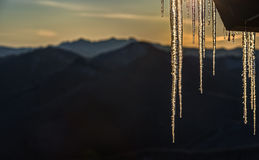 Icicles at Sunrise in cascade Mountains. Sunrise Silhouettes Cascade Mountains while Illuminating Hanging Icicle Formation Stock Photos
